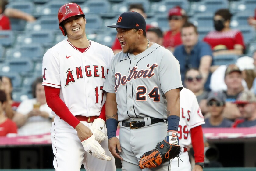 Los Angeles Angels' Shohei Ohtani, left, laughs with Detroit Tigers first baseman Miguel Cabrera at first during the first inning of a baseball game in Anaheim, Calif., Thursday, June 17, 2021. (AP Photo/Alex Gallardo)