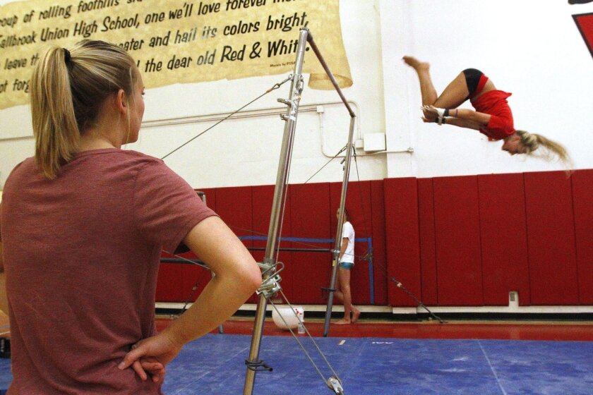 Fallbrook junior Sarah Engebretson dismounts from the uneven bars as coach Krystal Schmid looks on.