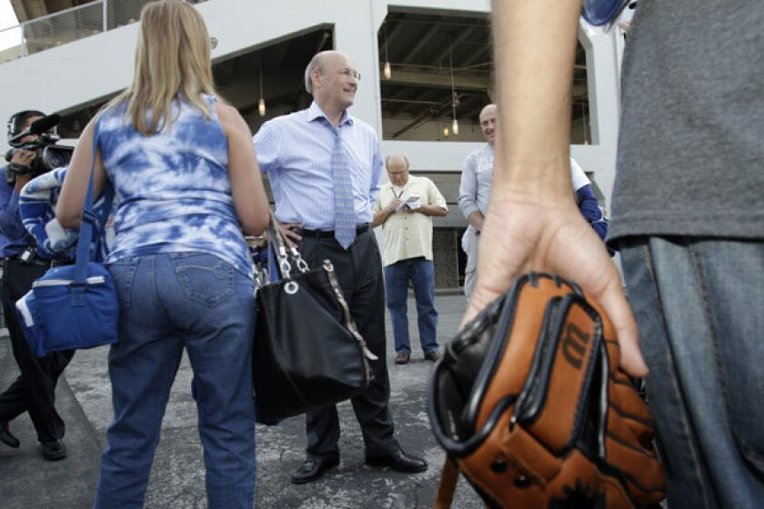 Dodgers' co¿owner Stan Kasten, center, greeting fans at the gate in Dodger Stadium.