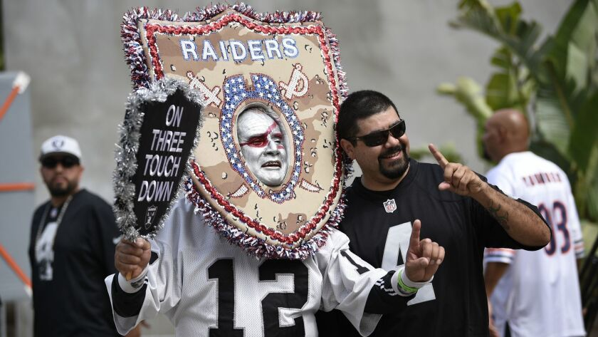 Oakland Raider fans pose before an NFL preseason football game against the Los Angeles Rams Saturday