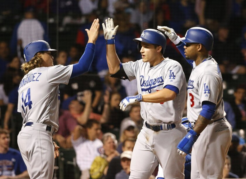 Los Angeles Dodgers' Corey Seager, center, is greeted at home by Enrique Hernandez (14) and Carl Crawford after the trio scored on Seager's home run off Chicago Cubs relief pitcher Trevor Cahill during the ninth inning of a baseball game Tuesday, May 31, 2016, in Chicago. (AP Photo/Charles Rex Arbogast)