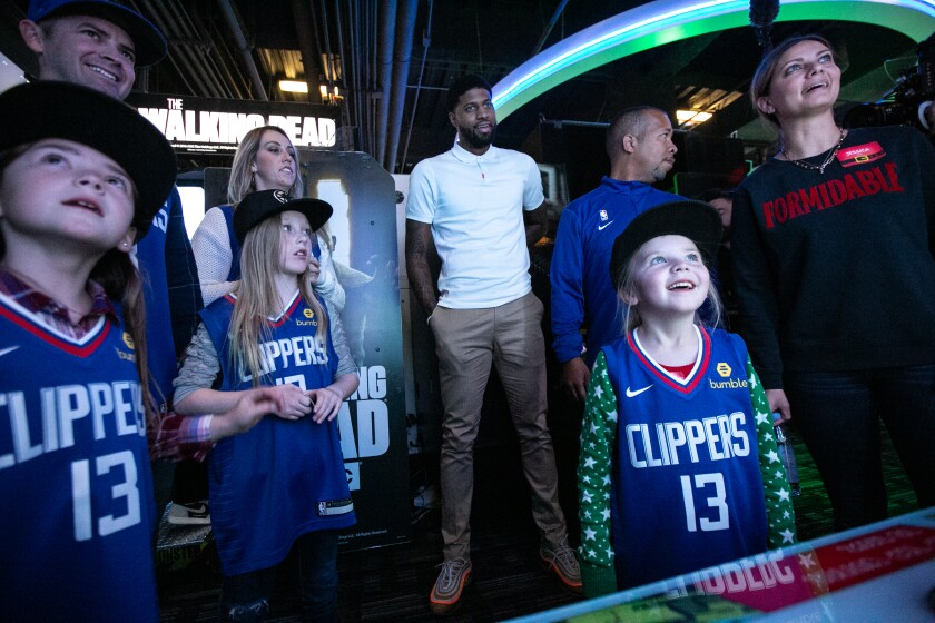 Reese Robertson, 5, right, plays a game with her family at Dave & Buster's as Clippers star Paul George, watching at rear, hosts his third annual Christmas celebration.
