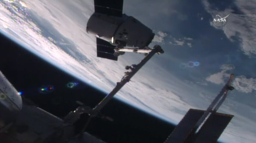 In this frame from NASA TV, the SpaceX Dragon capsule arrives at the International Space Station bearing supplies on Wednesday, July 20, 2016. The shipment includes a docking port needed for future rocket ships. (NASA TV via AP)