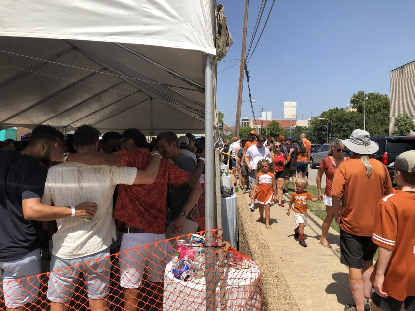 Longhorns fans pass a packed tailgating tent on their way to Saturday's game in Austin, Texas.