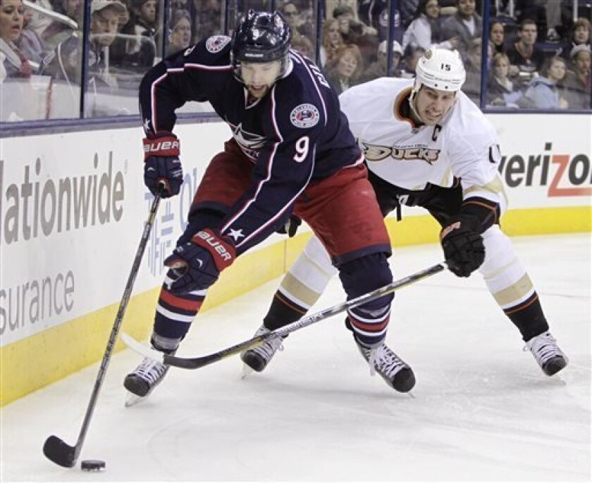 Columbus Blue Jackets' Colton Gillies, left, carries the puck behind the net as Anaheim Ducks' Ryan Getzlaf chases him during the second period of an NHL hockey game Sunday, March 31, 2013, in Columbus, Ohio. (AP Photo/Jay LaPrete)