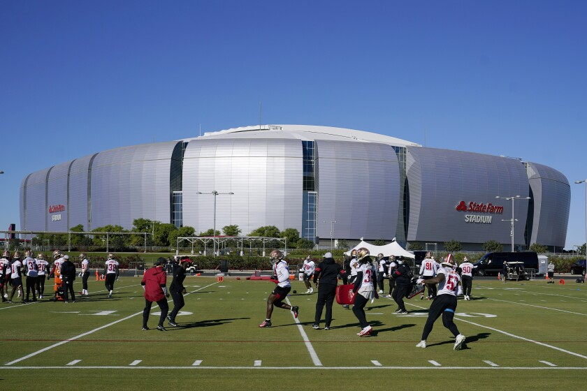 The San Francisco 49ers defensive players runs drills during practice in front of State Farm Stadium.