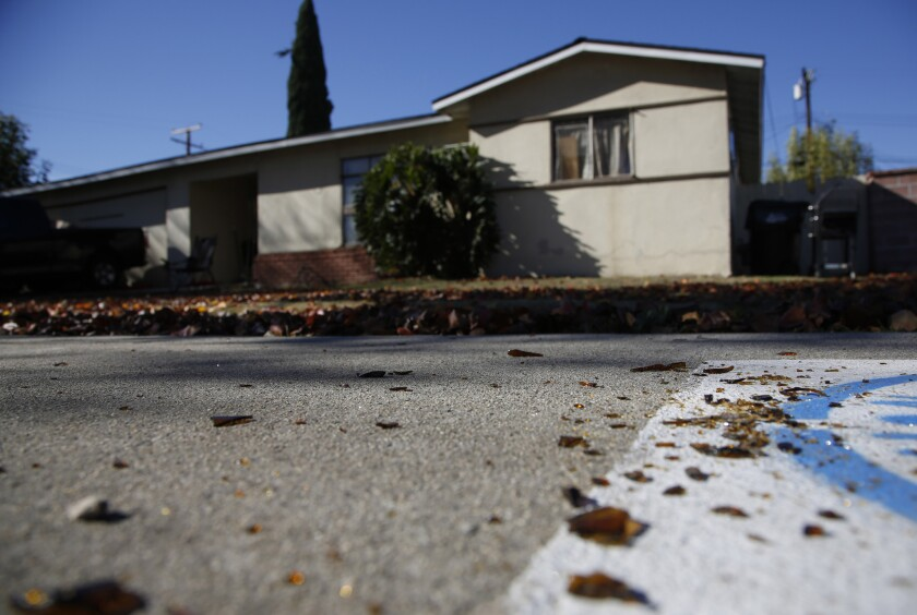 Broken glass near the sidewalk in front of a home in Rowland Heights where four people were killed, including the gunman, on New Year's Eve.