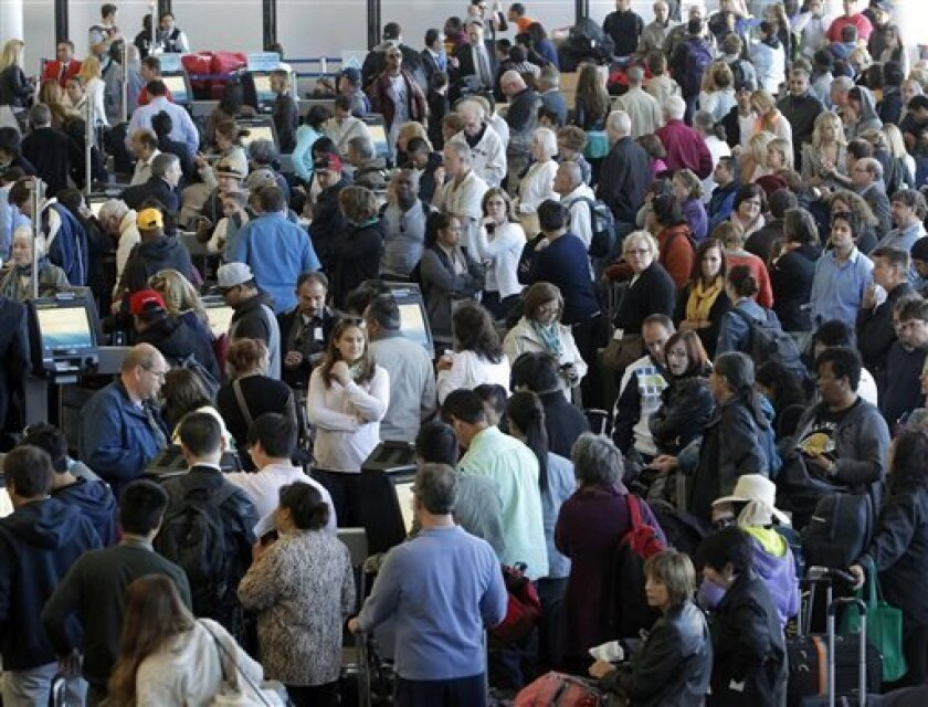 Passengers gather at the American Airlines check-in for flights at Los Angeles International Airport on Tuesday, April 16, 2013. Computer problems forced American Airlines to ground flights across the country Tuesday after the airline was unable to check passengers in and book passengers. (AP Photo