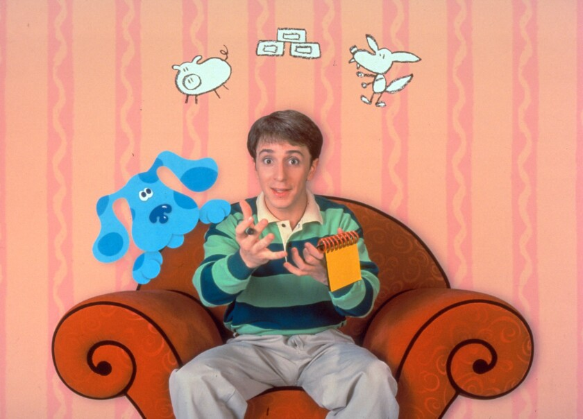 A young man sits on a chair surrounded by animated animals