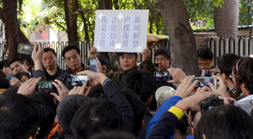A protester holds aloft a banner which shows freedom of speech near the headquarters of Southern Weekly newspaper in Guangzhou, Guangdong province.