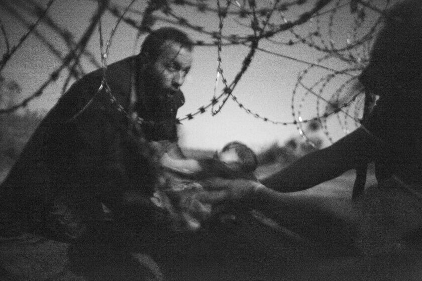 """In this image released by World Press Photo shows the World Press Photo of the Year titled """"Hope for a new Life"""" by photographer Warren Richardson. The picture also won a first prize in the Spot News singles category and shows a man passing a baby through the fence at the Serbia-Hungary border in R"""
