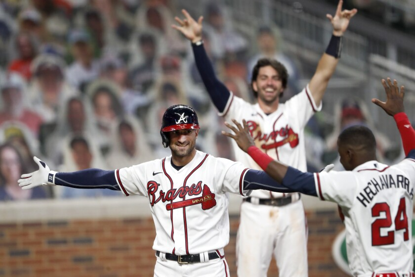 Atlanta Braves' Nick Markakis, left, celebrates with Adeiny Hechavarria (24) after hitting a game-winning home run in the ninth inning of a baseball game against the Atlanta Braves Thursday, Aug. 6, 2020, in Atlanta. (AP Photo/John Bazemore)