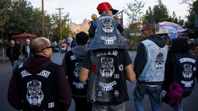 """Jose Avalos carries his son Nathan, 7, on his shoulders as members of the """"Dark Side Elite"""" social club walk to Cars Land at Disney California Adventure Park. The founders of a social club are accusing another club of intimidation and spreading false information."""
