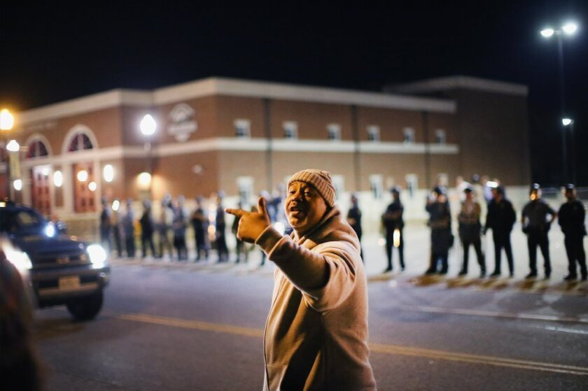 Police face off with demonstrators outside the police station in Ferguson, Mo.