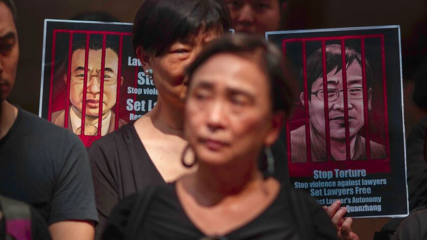 Portraits of detained Chinese human rights lawyers Wang Quanzhang, right, and Jian Tianyong are seen as Hong Kong pro-democracy activists protest in support of human rights lawyers in China on July 9, 2017.