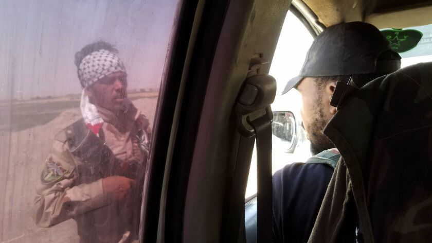 A Free Syrian Army fighter tries to hitch a ride out of East Raqqah Tuesday after others threatened