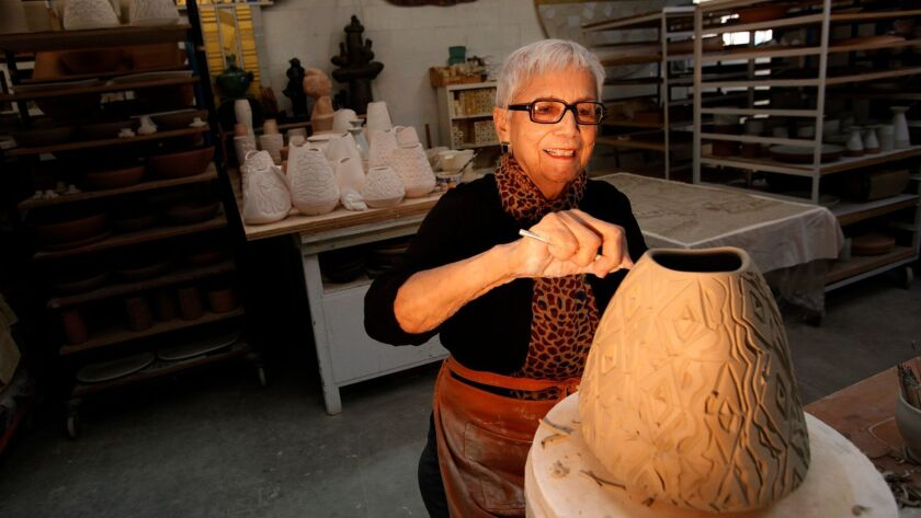 LOS ANGELES, CA - DECEMBER 22, 2014 -- Ceramic artist Dora De Larios works on a vase surrounded by o