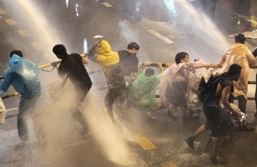Pro democracy demonstrators face water canons as police try to clear the protest venue in Bangkok, Thailand, Friday, Oct. 16, 2020. Thailand prime minister has rejected calls for his resignation as his government steps up efforts to stop student-led protesters from rallying in the capital for a second day in defiance of a strict state of emergency. (AP Photo/Gemunu Amarasinghe)