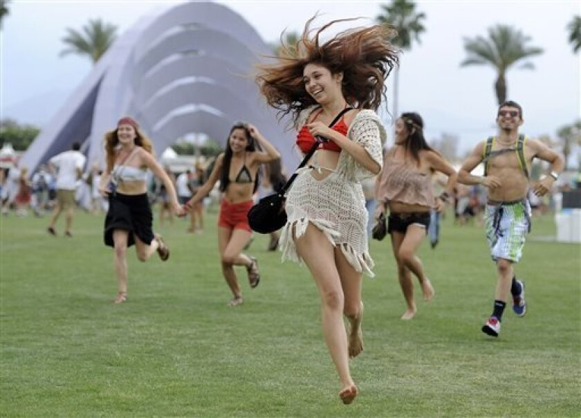 FILE - This April 13, 2012 file photo shows festivalgoers running toward the main stage to catch the beginning of Kendrick Lamar's set during the first weekend of the 2012 Coachella Valley Music and Arts Festival in Indio, Calif. New music festivals are popping up more quickly than you can count in