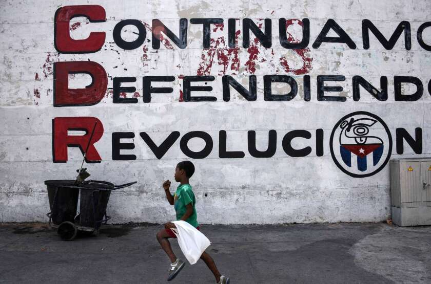 """In Havana on the eve of President Obama's visit, a child runs in front of a wall reading """"We keep defending the revolution."""""""