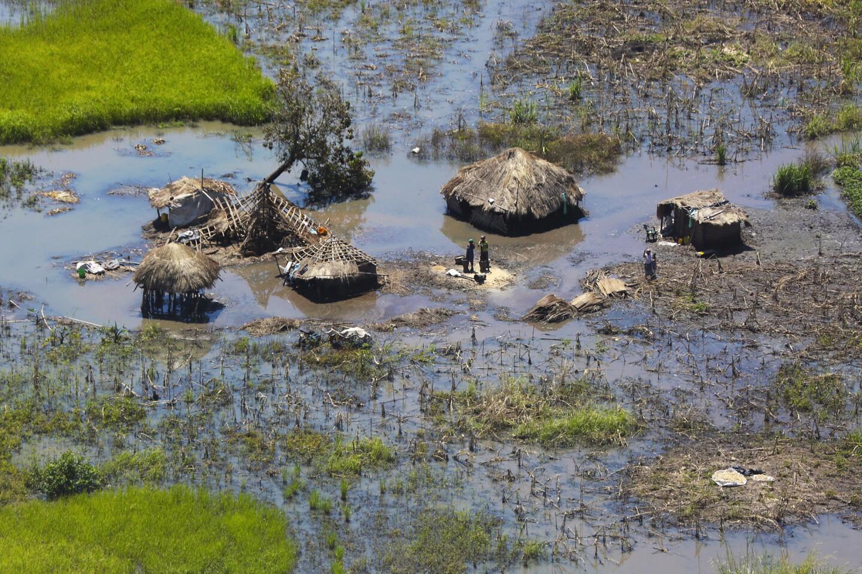 Unas personas aparecen alrededor de sus chozas destrozadas tras el paso del ciclón Idai en Nhamatanda, a unos 130 km de Beira, en Mozambique, el martes 26 de marzo del 2019. (AP Foto/Tsvangirayi Mukwazhi)