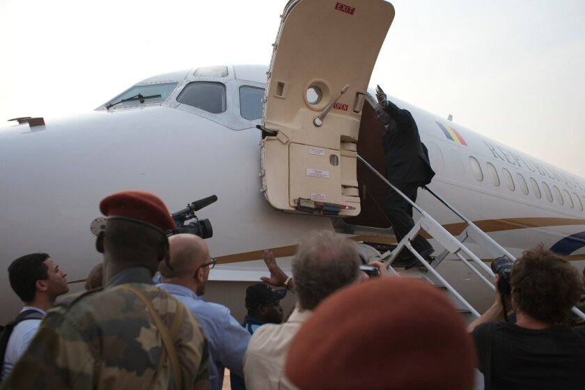 Central African Republic President Michel Djotodia gives a cursory wave as he boards a plane to Chad, at Mpoko Airport in Bangui, Central African Republic, Wednesday, Jan. 8, 2014. The embattled president, who has come under growing pressure to resign, traveled to neighboring Chad on Wednesday for a summit with regional leaders who want to end the bloodshed that has left more than 1,000 dead and nearly a million people displaced.(AP Photo/Rebecca Blackwell)