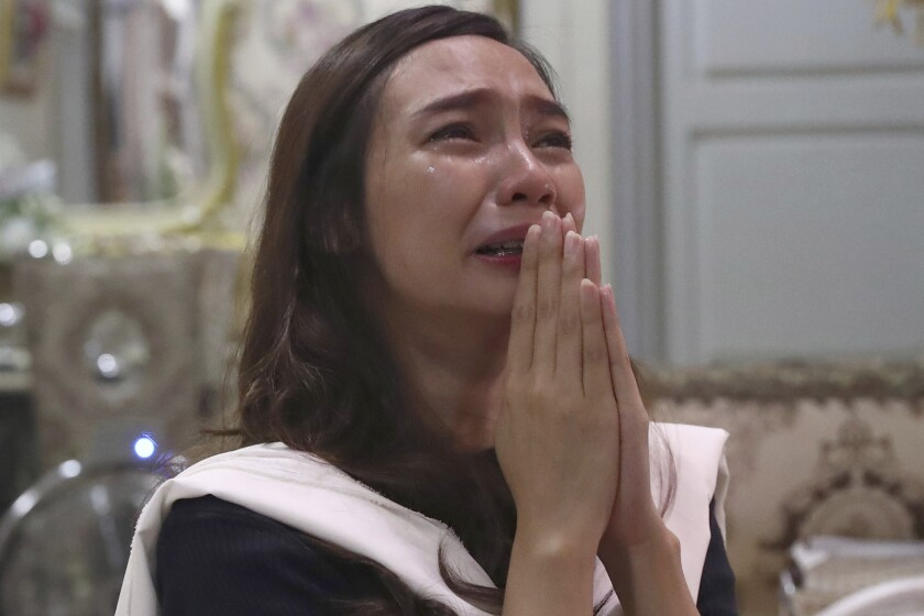 Tri Novia Septiani cries during an online memorial service marking the 40th day since the death of her fiance Dr. Michael Robert Marampe who died of COVID-19, in Jakarta, Indonesia, on June 5, 2020. Marampe knew what he wanted to be since he was a kid: a doctor and a pianist. He became both, and his passion for music even led him to Septiani - a woman he never got to marry because he got the coronavirus. Marampe became one of dozens of doctors the coronavirus has claimed so far in Indonesia. (AP Photo/Tatan Syuflana)