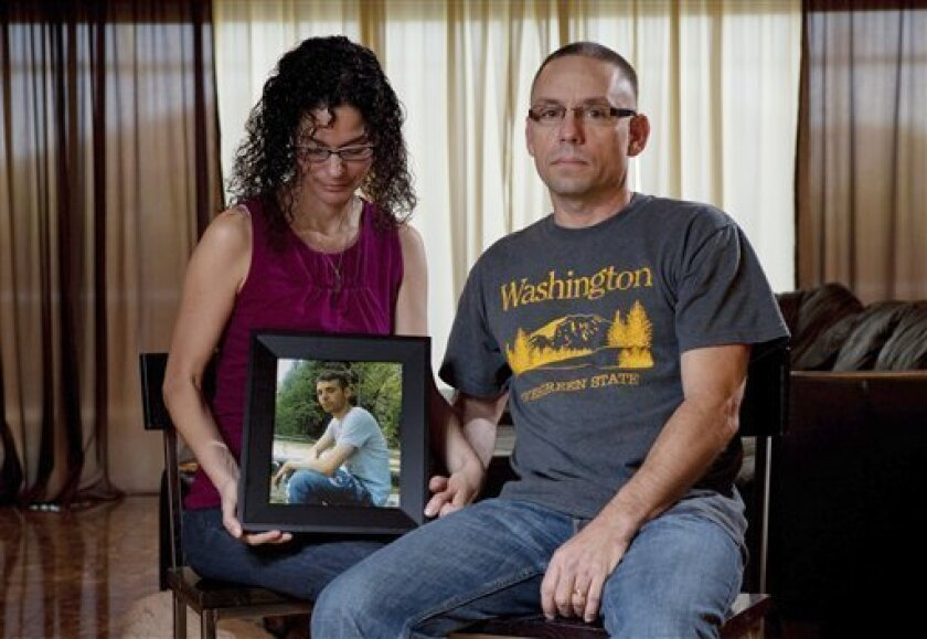 Emma and Christopher Winfield hold a photograph of their son, 22-year-old U.S. Army Spc. Adam Winfield, at their home in Cape Coral, Fla., Friday, Sept. 3, 2010. Adam is accused of murdering civilians during his deployment to Afghanistan, a charge he and his family firmly refute. (AP Photo/Erik Kellar)