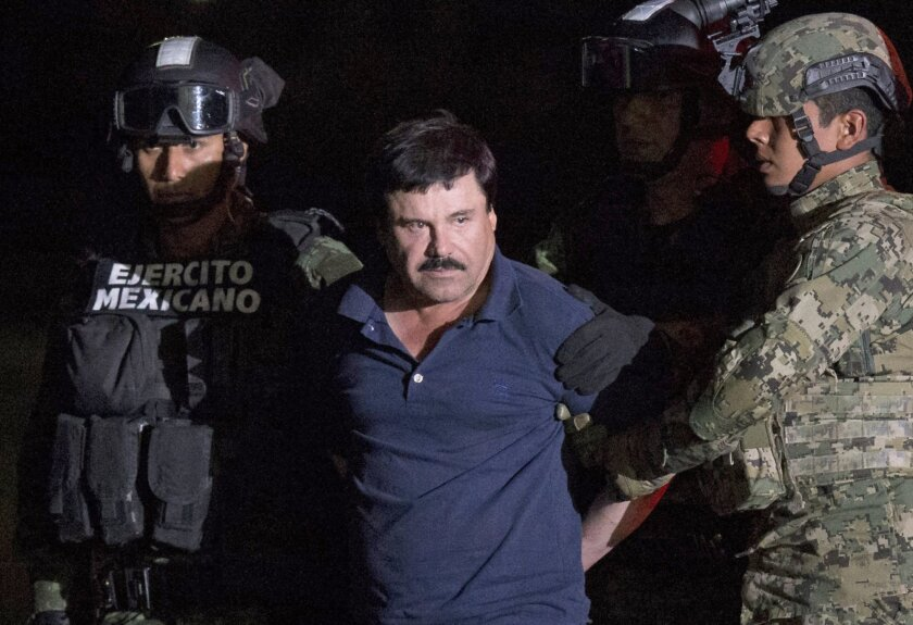 """Mexican drug lord Joaquin """"El Chapo"""" Guzman is escorted by army soldiers to a waiting helicopter, at a federal hangar in Mexico City, Friday, Jan. 8, 2016. The world's most wanted drug lord was recaptured by Mexican marines Friday, six months after he fled through a tunnel from a maximum secuirty prison in a made-for-Hollywood escape that deeply embarrassed the government and strained ties with the United States. (AP Photo/Rebecca Blackwell)"""