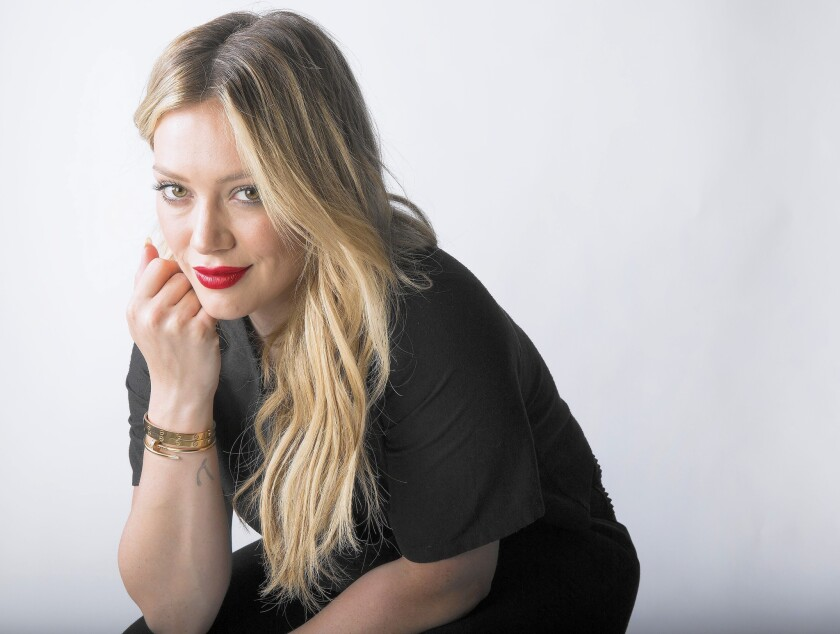 Hilary Duff sits in a black T-shirt and pants, chin resting on her hand