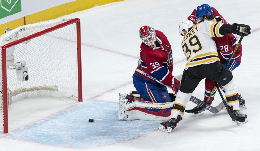 Montreal Canadiens' goalie Mike Condon (39) looks back at a loose puck as defenseman Nathan Beaulieu (28) tries to hold back Boston Bruins' Matt Beleskey (39) during second period NHL hockey action, in Montreal, on Saturday, Nov. 7, 2015. (Paul Chiasson/The Canadian Press via AP)