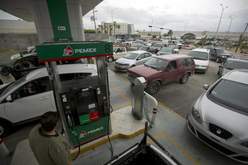 Drivers wait in line to fill up their gas tanks in preparation for the arrival of Hurricane Newton in Cabo San Lucas, Mexico, Monday Sept. 5, 2016. Authorities at the southern end of Mexico's Baja California peninsula ordered schools closed and set up emergency shelters as Hurricane Newton gained s