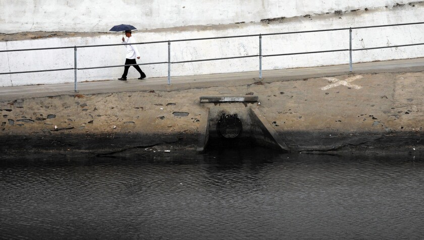 A pedestrian walks on a path along Ballona Creek, which drains part of the Los Angeles Basin and carries contaminated runoff to Santa Monica Bay.