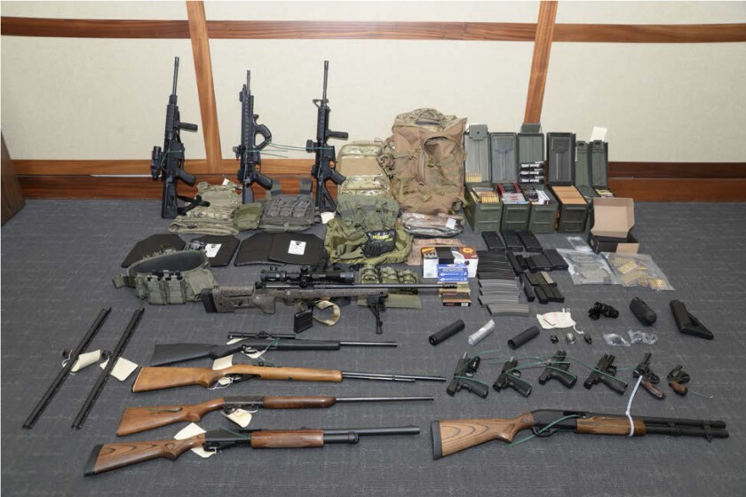 """FILE - This file image provided by the Maryland U.S. District Attorney's Office shows a photo of firearms and ammunition that was in the motion for detention pending trial in the case against Christopher Paul Hasson. Prosecutors say that Hasson, a Coast Guard lieutenant is a """"domestic terrorist"""" who wrote about biological attacks and had a hit list that included prominent Democrats and media figures. Hasson is expected to plead guilty Thursday, Oct. 3, 2019 in a case charging him with gun and drug offenses. (Maryland U.S. District Attorney's Office via AP, File)"""