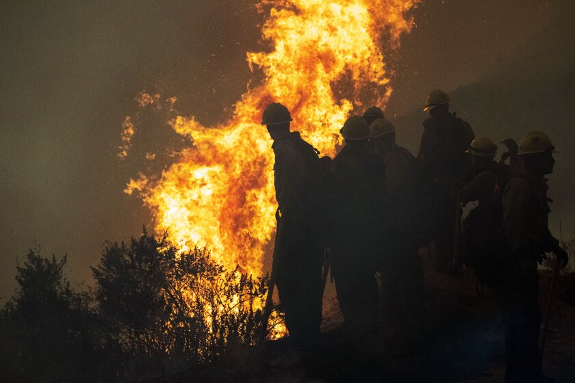 Firefighters monitor a controlled burn along Nacimiento-Fergusson Road to help contain the Dolan Fire near Big Sur, Calif., Friday, Sept. 11, 2020. (AP Photo/Nic Coury)