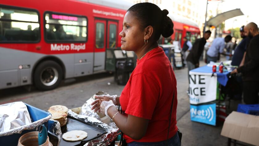 Yesenia Rodriguez, 34, makes pupusas in MacArthur Park. She came to the United States from El Salvador with her son, who is now 16, in 2014.