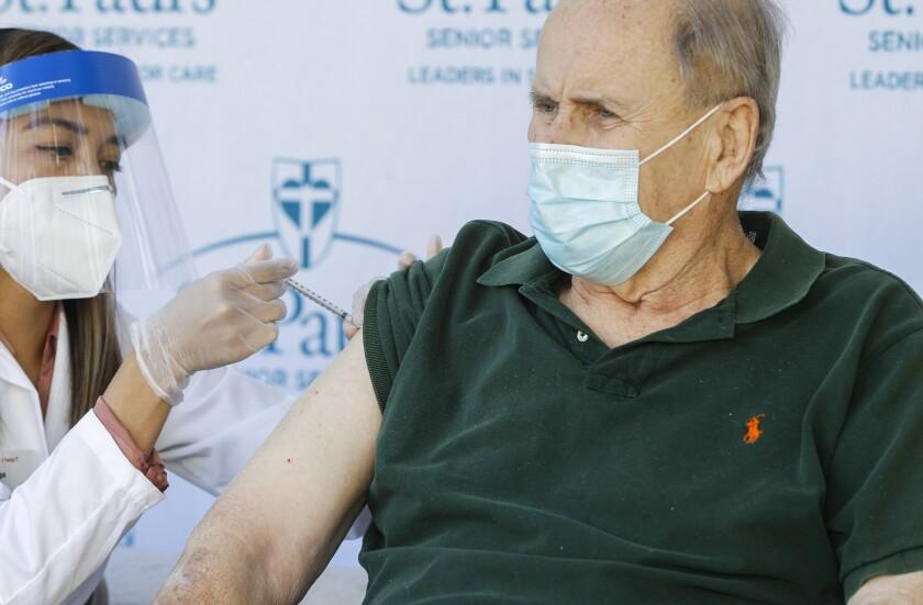 Resident Eldon Thompson (right) gets his vaccination shot from pharmacist Rachel Diega at St. Paul's McColl Health Center