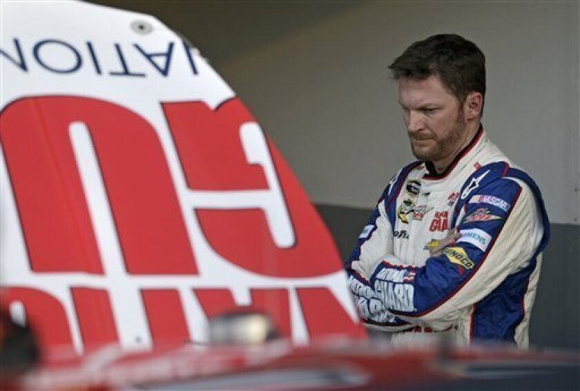 Dale Earnhardt Jr. looks under the hood as crew members makes adjustments to his car after practice for the NASCAR Sprint Unlimited Shootout auto race at Daytona International Speedway, Friday, Feb. 15, 2013, in Daytona Beach, Fla. (AP Photo/John Raoux)