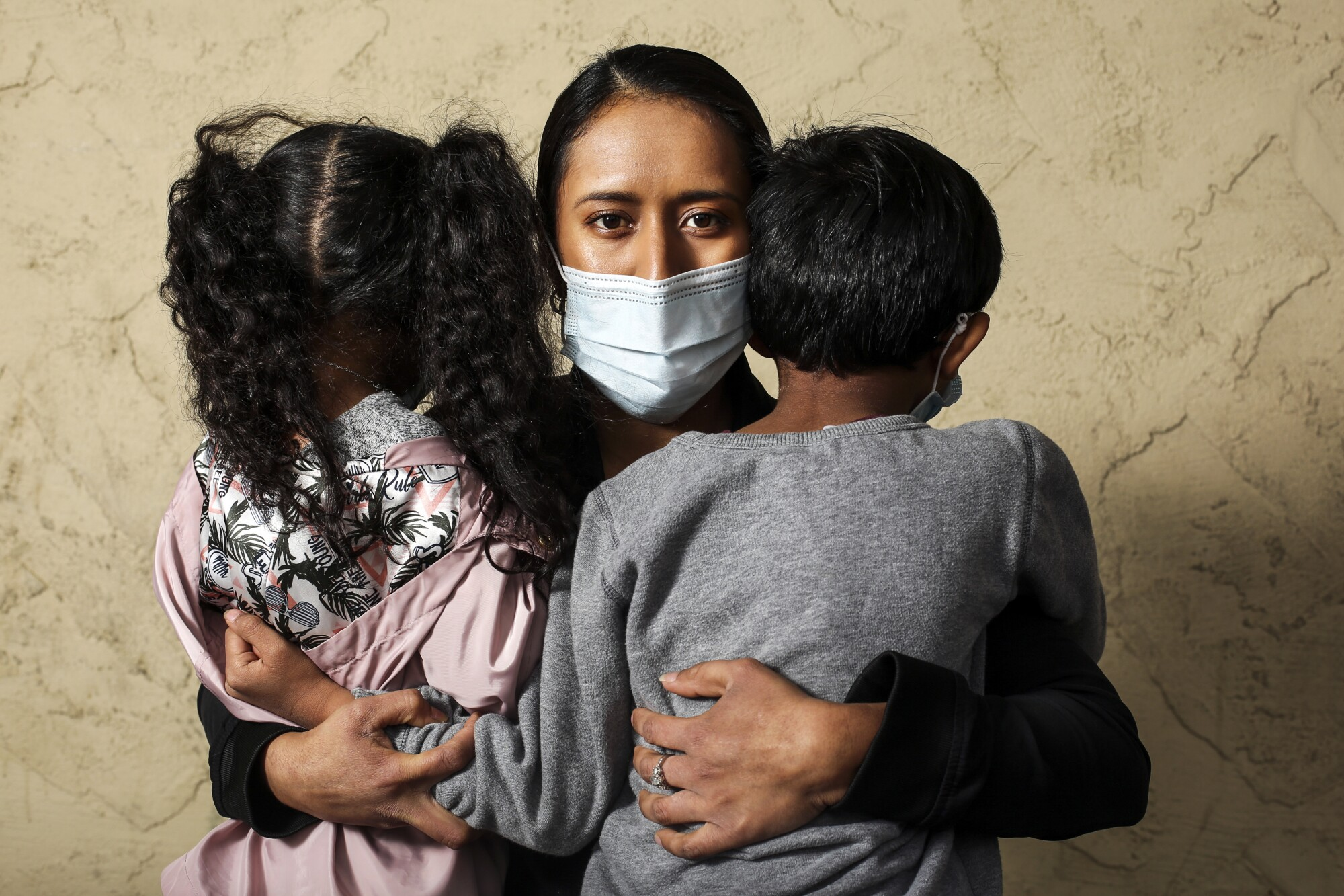 A woman holds her children