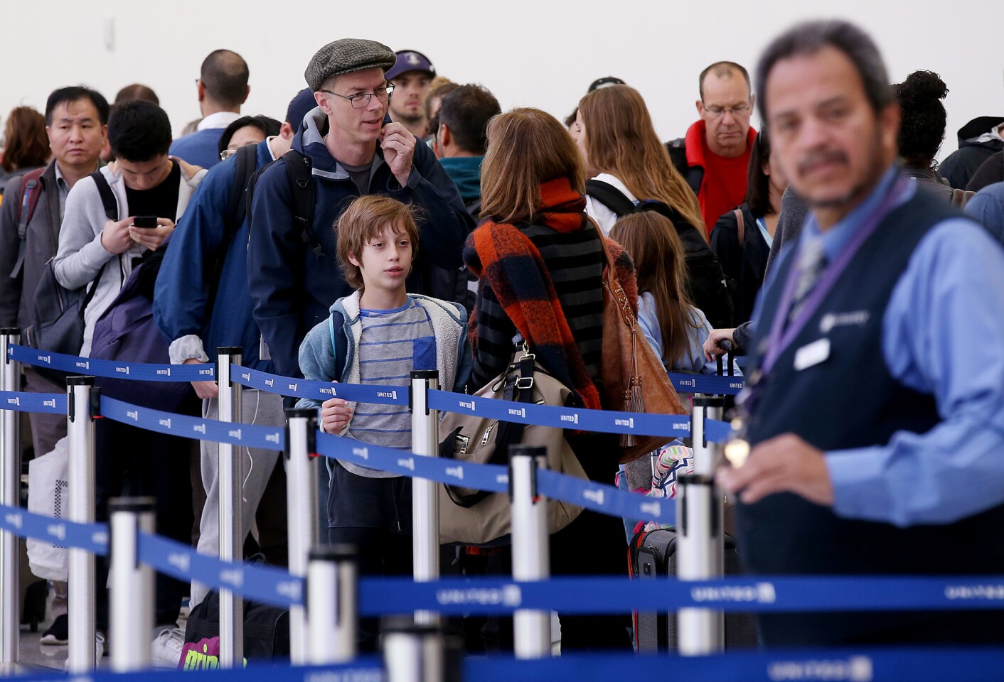 Holiday travelers line up for security screenings in Terminal 7 at LAX on Thursday. Airport officials said nearly 230 flights have been either canceled or delayed.
