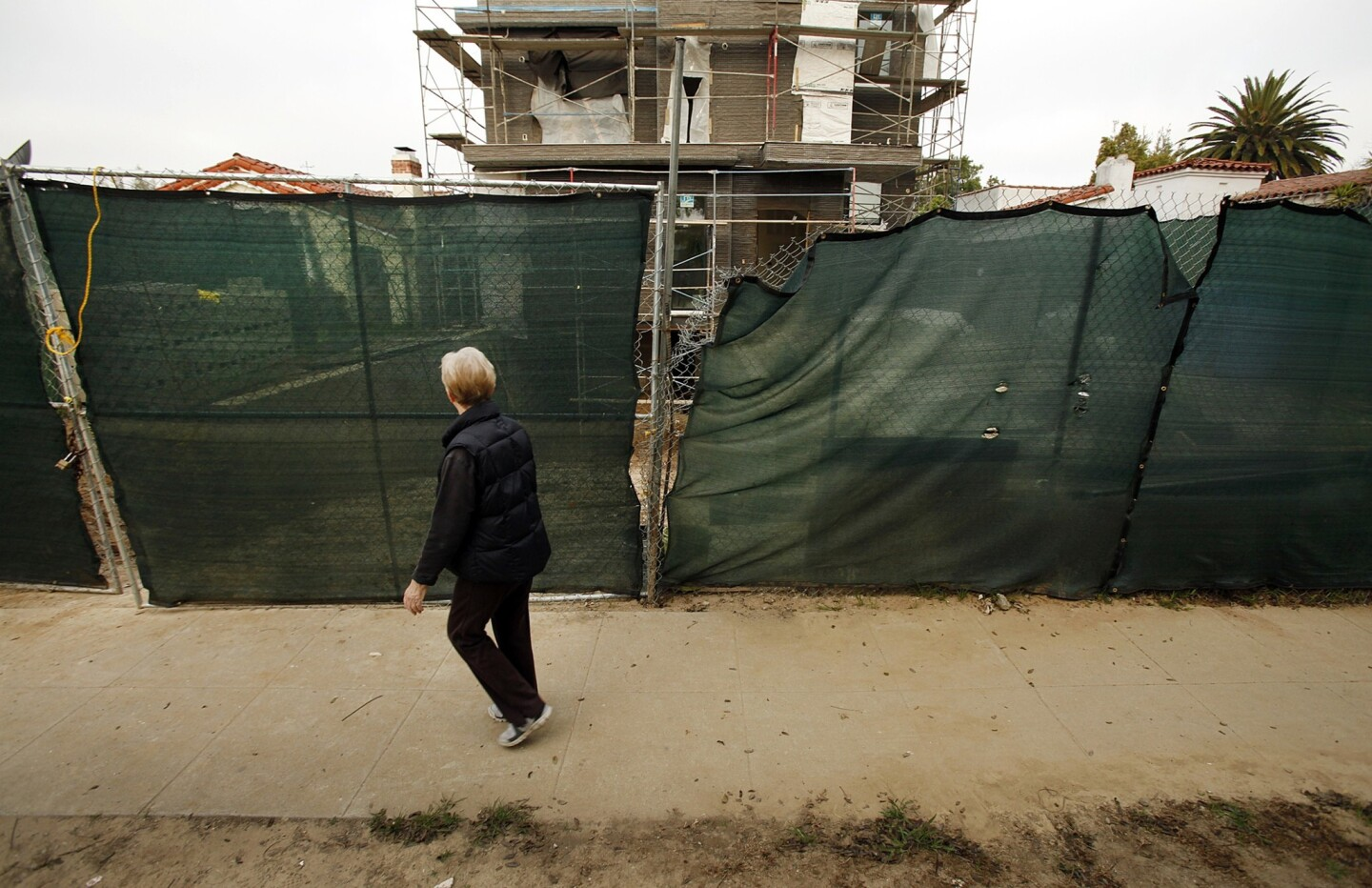 """Bea Samples, who lives a few doors away, walks past a home under construction in Faircrest Heights. Neighbors believe several homes under construction in the area demonstrate examples of """"mansionization"""" and are trying to bring attention to them."""