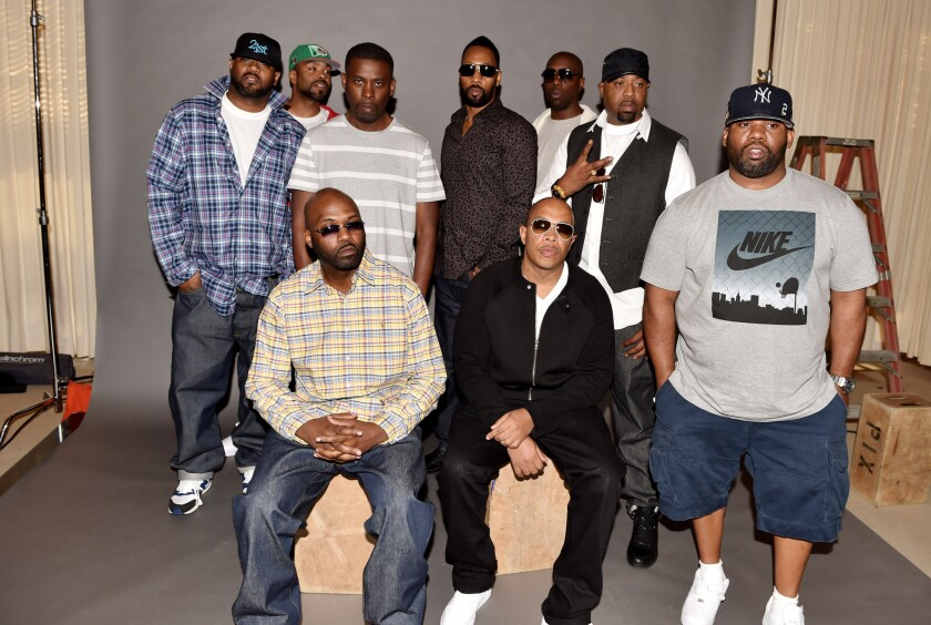 Rappers Masta Killa (seated, left), U-God and, standing from left, Ghostface Killah, Method Man, GZA, RZA, Inspectah Deck, Cappadonna and Raekwon announce they have signed with Warner Bros. Records in Burbank.