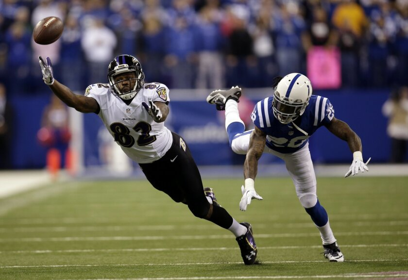 The ball falls out of reach of Baltimore Ravens wide receiver Torrey Smith, left, as he defended by Indianapolis Colts cornerback Greg Toler on a fourth down play in the final minute of an NFL football game in Indianapolis, Sunday, Oct. 5, 2014. The Colts defeated the Ravens 20-13. (AP Photo/AJ Mas