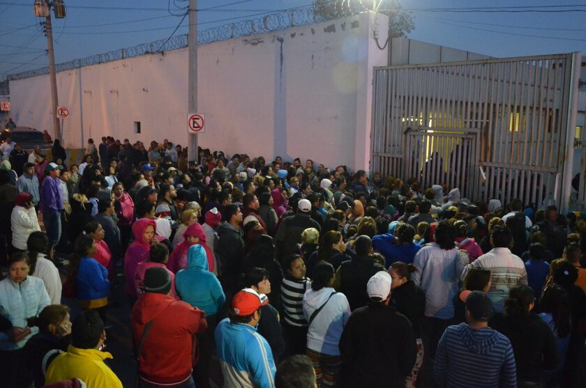 In this Thursday, Feb. 11, 2016 photo, relatives of inmates stand outside the Topo Chico prison, where a riot broke out overnight in Monterrey, Mexico. Dozens of inmates were killed and several injured in a brutal fight between two rival factions at the prison in northern Mexico, according to the s