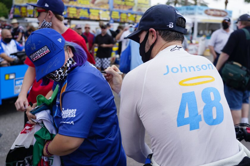 IndyCar driver Jimmie Johnson (48) signs the shirt of fan Caroline Gast of Sarasota after the morning practice session at the Grand Prix of St. Petersburg auto race, Sunday, April 25, 2021 in St. Petersburg, Fla. (Luis Santana/Tampa Bay Times via AP)