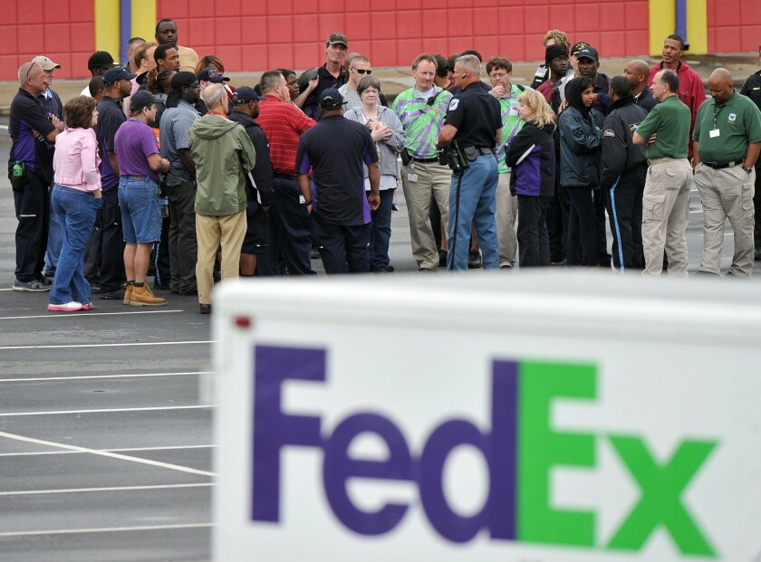 A Cobb County Police Officer speaks to FedEx employees and family members gathered at the parking lot of a skating rink located near the shipping facility where a gunman open fire in Kennesaw, Ga., on Tuesday, April 29, 2014.  A shooter described as being armed with an assault rifle and having bull
