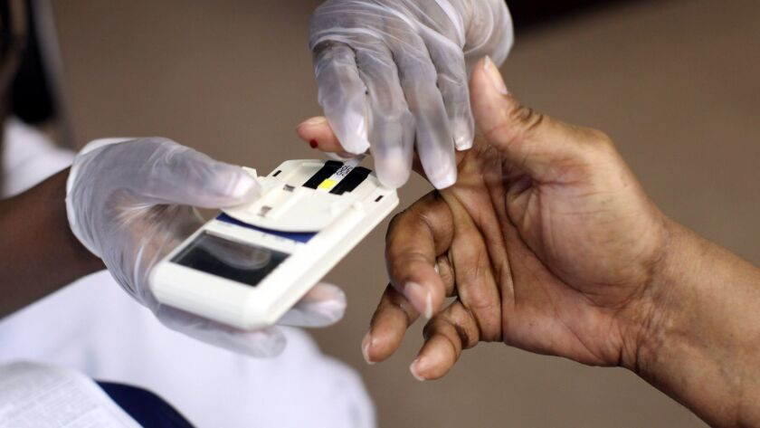 NEWARK, NJ - AUGUST 13: A mans finger is pricked to test his cholesterol at the City of Newark's fr