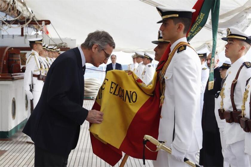 """El embajador de España en Estados Unidos, Santiago Cabanas (izq), besa la bandera de España durante un acto celebrado este martes en el buque-escuela de la Armada española """"Juan Sebastián de Elcano"""", en San Juan (Puerto Rico). EFE"""