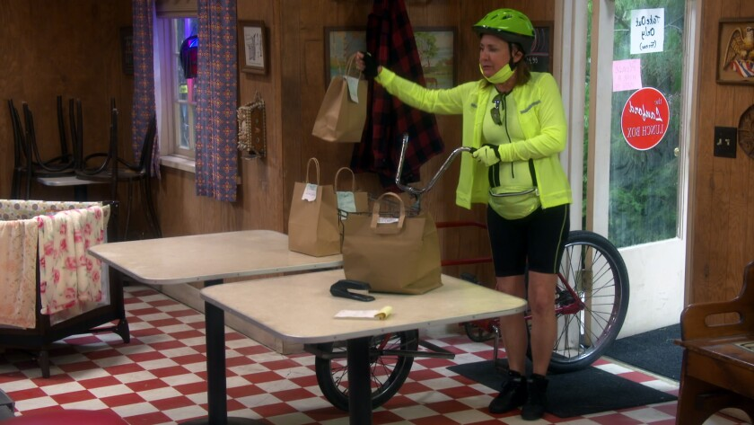 """Laurie Metcalf does food deliveries by bike in the season premiere of """"The Conners."""""""