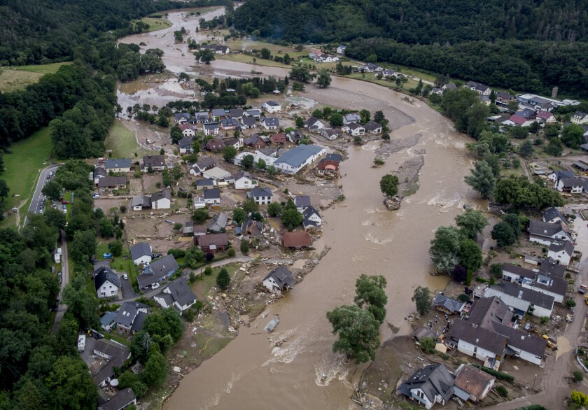 FILE - In this July 15, 2021 file photo the Ahr river floats past destroyed houses in Insul, Germany. Due to heavy rain falls the Ahr river dramatically went over the banks the evening before. The mayors of three German towns badly hit by last month's deadly floods are appealing for more help from the state and federal governments, saying the disaster caused billions of euros (dollars) worth of damage. (AP Photo/Michael Probst, file)